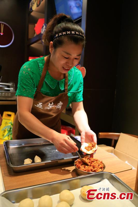 A cook prepares mooncakes stuffed with crayfish at a restaurant in Hangzhou City, the capital of East China's Zhejiang Province, Sept. 29, 2017. The restaurant is experimenting with using novel ingredients in their mooncakes, a must-have delicacy for the Mid-Autumn Festival, to boost business. (Photo: China News Service/Wang Yuan)