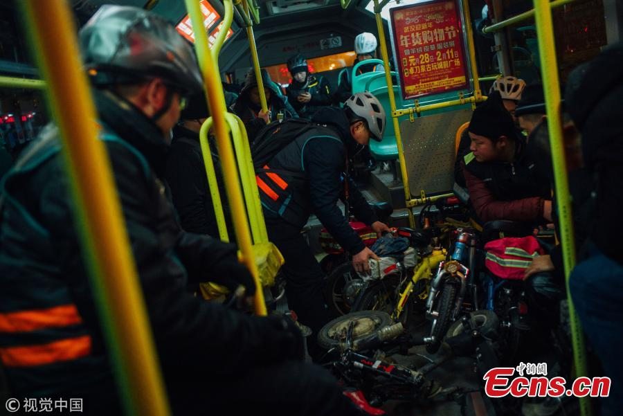 Passengers, mostly chauffeurs, ride a bus for free in Wuhan City, the capital of Central China's Hubei Province, Feb. 7, 2018. Chauffeurs see an increase in demand for their services as more car owners drink more alcohol at dinners and parties ahead of Spring Festival, China's Lunar New Year. Chauffeurs usually ride their folding bicycles to restaurants and entertainment venues, pick customers up there, and drive them home in their own cars. Some can earn up to 800 yuan ($120) over one night for the service. (Photo/VCG)