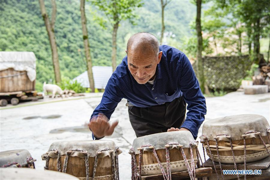 Wu Kaixue checks the sound of Dingtang drums at his courtyard in Longtan Village, Shennongjia of central China\'s Hubei Province, May 21, 2018. Wu Kaixue, who is 75 years old, began to learn the making of Dingtang drums when he was 13. The making of Dingtang drums needs natural resources from the Shennongjia forest and also requires high standard of techniques. Wu makes 100 plus drums in a year and his fame has spread far away. (Xinhua/Du Huaju)