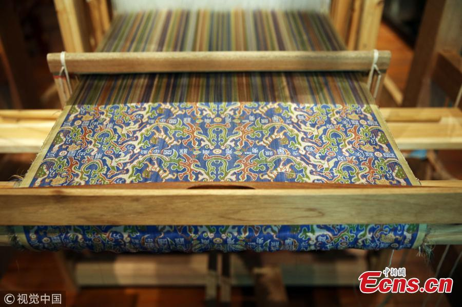 "A replica of a colorful brocade embroidered with the text ""Wuxing Chu Dongfang Li Zhongguo"", which literary means \"