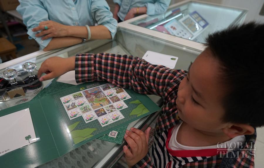 A boy, accompanied by his mother, stamps his souvenir travelling frog stamp folder. (Photo: Xiang Jun/GT)