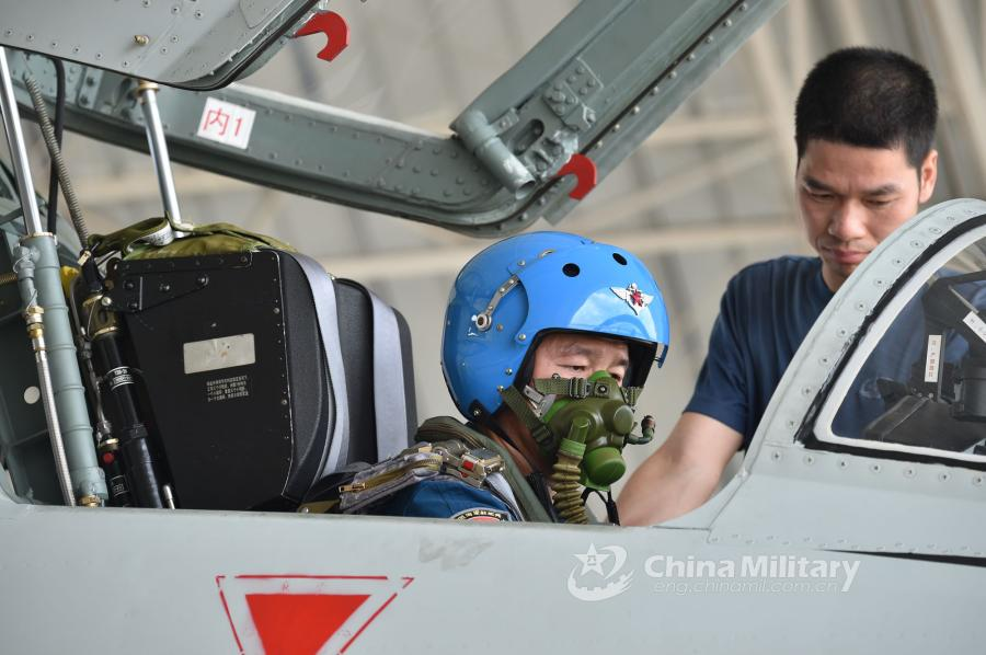 A pilot assigned to an aviation brigade of the South China Sea Fleet under the PLA Navy goes through pre-flight procedures prior to a live-fire training exercise at a shooting range in the South China Sea from May 17 to 18, 2018. (Photo/eng.chinamil.com.cn)