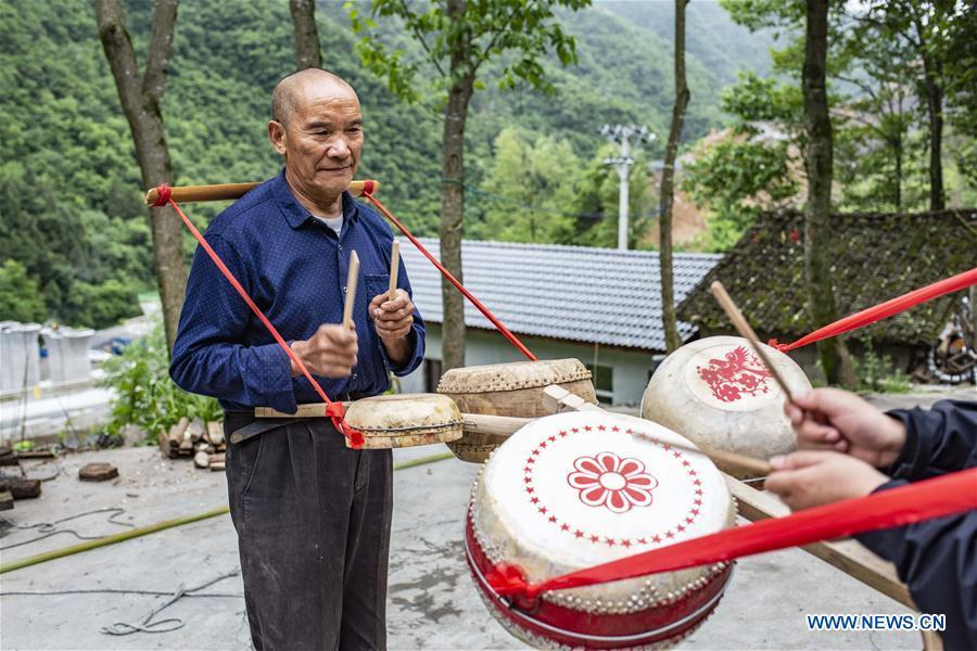 Wu Kaixue shows how to beat the Dingtang drum at his courtyard in Longtan Village, Shennongjia of central China\'s Hubei Province, May 21, 2018. Wu Kaixue, who is 75 years old, began to learn the making of Dingtang drums when he was 13. The making of Dingtang drums needs natural resources from the Shennongjia forest and also requires high standard of techniques. Wu makes 100 plus drums in a year and his fame has spread far away. (Xinhua/Du Huaju)