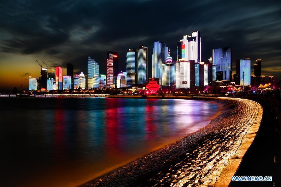 Photo taken on April 14, 2018 shows the night view of Fushan Bay in Qingdao, a coastal city in east China\'s Shandong Province. Home to Tsingtao Beer and home appliance giant Haier, Qingdao is becoming a more attractive place to run important multilateral events. In June, the coastal city will host the 18th summit of the Shanghai Cooperation Organization (SCO). (Xinhua/Guo Xulei)