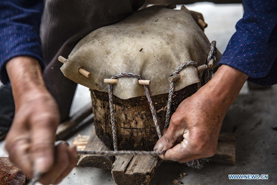 Wu Kaixue makes a Dingtang drum at his courtyard in Longtan Village, Shennongjia of central China\'s Hubei Province, May 21, 2018. Wu Kaixue, who is 75 years old, began to learn the making of Dingtang drums when he was 13. The making of Dingtang drums needs natural resources from the Shennongjia forest and also requires high standard of techniques. Wu makes 100 plus drums in a year and his fame has spread far away. (Xinhua/Du Huaju)