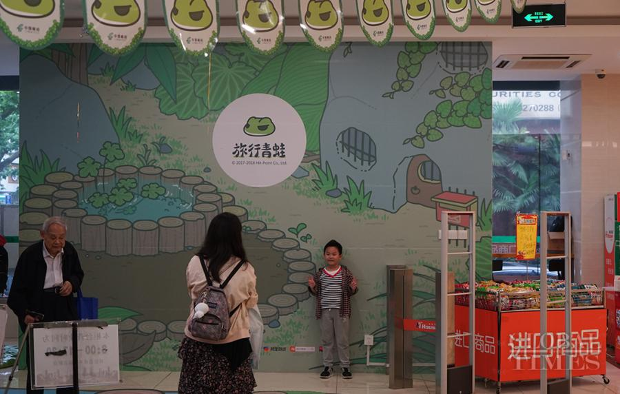 A boy poses in front of a travelling-frog themed background. (Photo: Xiang Jun/GT)