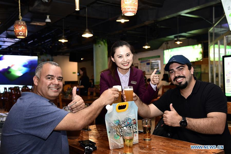 Tourists toast with Tsingtao Beer in Qingdao, a coastal city in east China\'s Shandong Province, May 17, 2018. Home to Tsingtao Beer and home appliance giant Haier, Qingdao is becoming a more attractive place to run important multilateral events. In June, the coastal city will host the 18th summit of the Shanghai Cooperation Organization (SCO). (Xinhua/Guo Xulei)