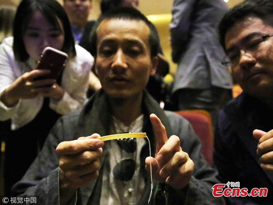 Artist Chen Xuanpeng shows a mouth harp made of bone at the Xi′an Conservatory of Music in Xian City, Northwest China's Shaanxi Province, May 21, 2018. The musical instrument excavated from the Shimao ruins in Shenmu City measures about 9 centimeters long by 1 centimeter wide and is 2 millimeters thick. It is estimated to have been made 4,000 years ago. Some 20 such mouth harps made of bone were found at the ruins. (Photo/VCG)
