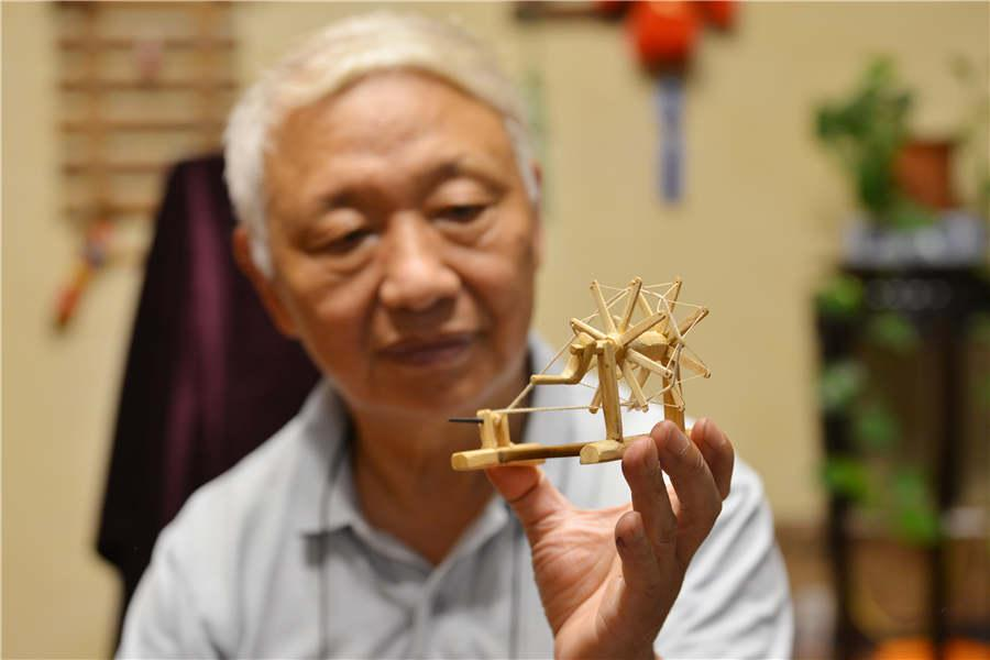 Chen Hesheng shows a miniature wooden spinning wheel. (Photo/Asianewsphoto)