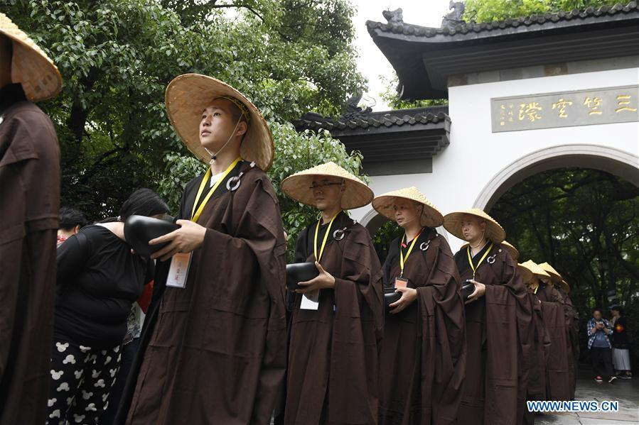 Monks holding bowls receive donation from residents and tourists in Hangzhou, capital of east China\'s Zhejiang Province, on May 22, 2018. Altogether 1,000 monks in Hangzhou participated in a traditional mendicants\' walk on Tuesday to walk from Faxi Temple to Lingyin Temple for charity. All the donation received along the way will be donated to charity.(Xinhua/Huang Zongzhi)