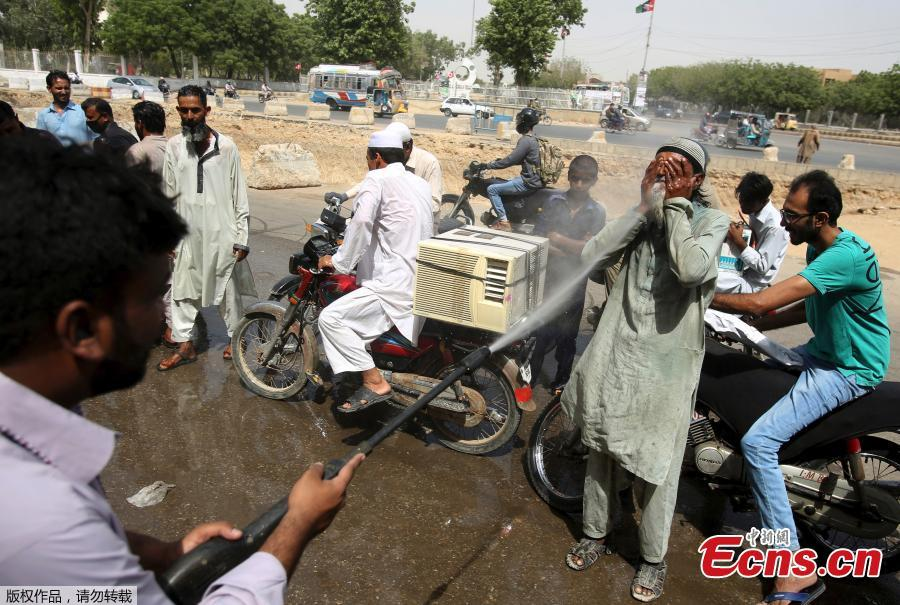 Pakistani volunteer spray water on people to keep them cool in Karachi, Pakistan, May 21, 2018. The Meteorological Department has issued a heat-wave alert for three days. (Photo/Agencies)