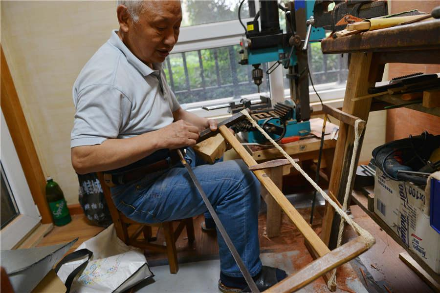 Chen Hesheng makes wooden items using a saw which he has used for 52 years. (Photo/Asianewsphoto)