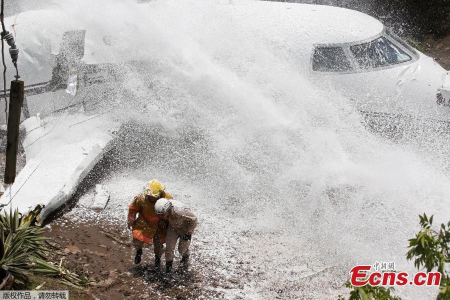 Firefighters take cover from firefighting foam applied onto the wreckage of a Gulfstream G200 aircraft that skidded off the runway during landing at Toncontin International Airport in Tegucigalpa, Honduras, May 22, 2018. At least six passengers were injured. (Photo/Agencies)