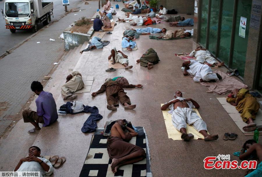 Residents sleep on a building pavement, to escape heat and frequent power outage in their residence area Karachi, Pakistan, May 22, 2018. The Meteorological Department has issued a heat-wave alert for three days. (Photo/Agencies)