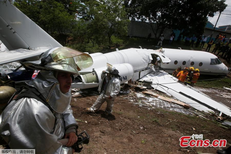 Firefighters stand near a Gulfstream G200 aircraft that skidded off the runway during landing at Toncontin International Airport in Tegucigalpa, Honduras, May 22, 2018. At least six passengers were injured. (Photo/Agencies)