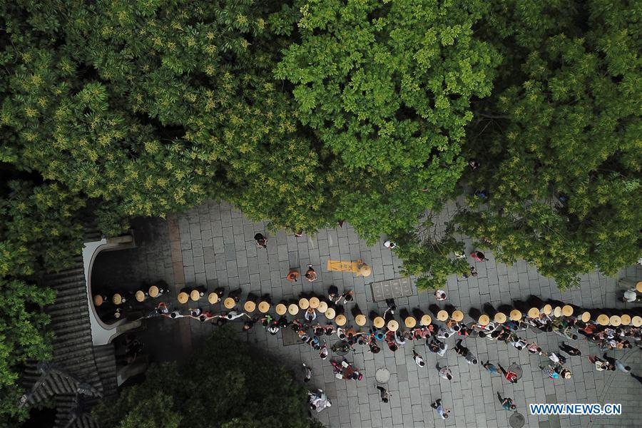 Monks holding bowls walk towards Lingyin Temple in Hangzhou, capital of east China\'s Zhejiang Province, on May 22, 2018. Altogether 1,000 monks in Hangzhou participated in a traditional mendicants\' walk on Tuesday to walk from Faxi Temple to Lingyin Temple for charity. All the donation received along the way will be donated to charity.(Xinhua/Huang Zongzhi)