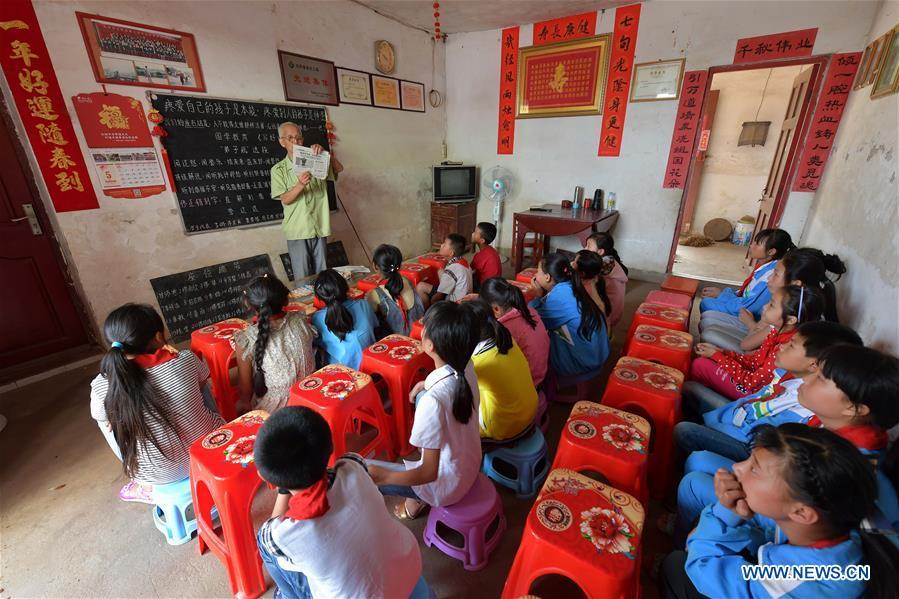 Miao Yanxiang reads a report of good deeds for children at the caring station for left-behind children at his home in Shibu Town, Nanchang City of east China\'s Jiangxi Province, May 23, 2018. Miao, over 70, established a caring station for left-behind children at his own house in 2009, where he provided free place for children to do homework and study after school. Having received more than 3,000 children over the past nine years, Miao is satisfied with his voluntary work as he see the progress of the children. (Xinhua/Peng Zhaozhi)