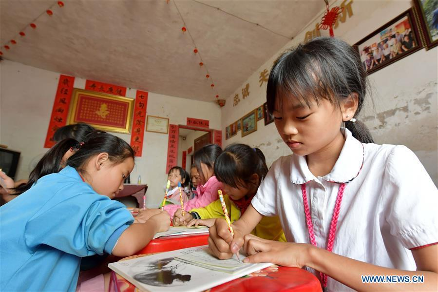 Children do homework at the caring station for left-behind children at Miao Yanxiang\'s home in Shibu Town, Nanchang City of east China\'s Jiangxi Province, May 23, 2018. Miao, over 70, established a caring station for left-behind children at his own house in 2009, where he provided free place for children to do homework and study after school. Having received more than 3,000 children over the past nine years, Miao is satisfied with his voluntary work as he see the progress of the children. (Xinhua/Peng Zhaozhi)