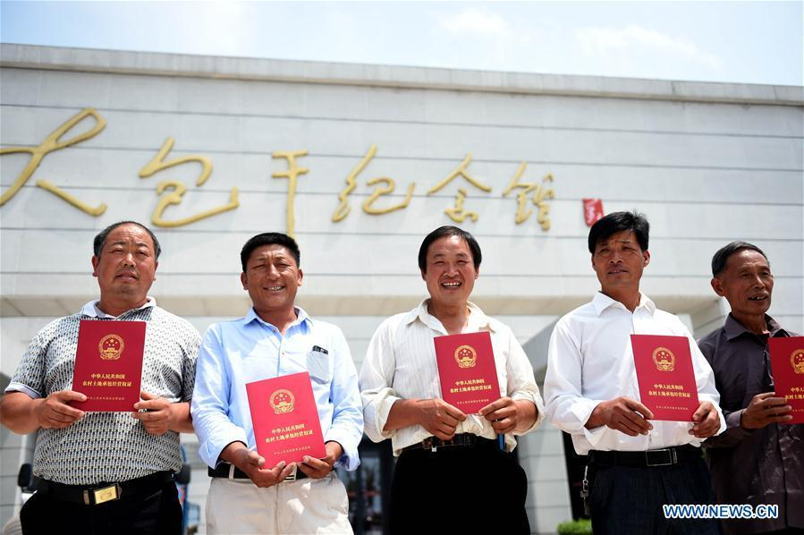 Farmers show rural land contract of management warrants at Xiaogang Village in Fengyang County, east China\'s Anhui Province, July 8, 2015. This year marks the 40th anniversary of China\'s starting to implement reform and opening up policy. (Xinhua/Liu Junxi)