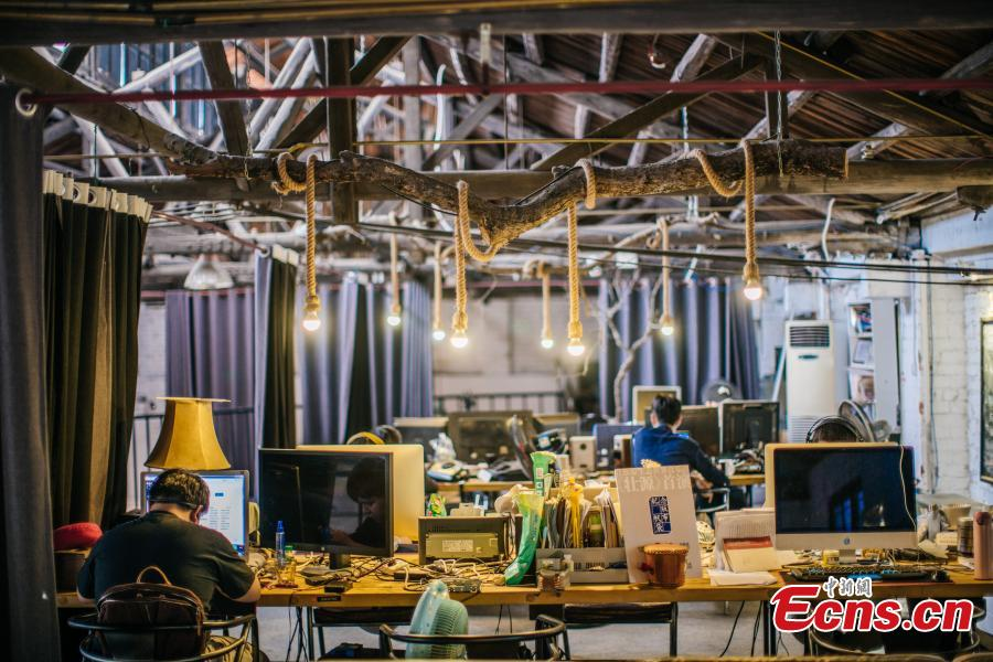 Three young people have transformed an abandoned room of a walking tractor factory into a modern office space for their cultural creations in Nanning City, South China's Guangxi Zhuang Autonomous Region. Xu Xiaomao, Ouyang Dinghua and Wei Ning rented the space in April 2015 and renovated it for their startup in video and music production. The closed tractor factory was built in 1956 of the former Soviet style. (Photo: China News Service/Liu Yujun)