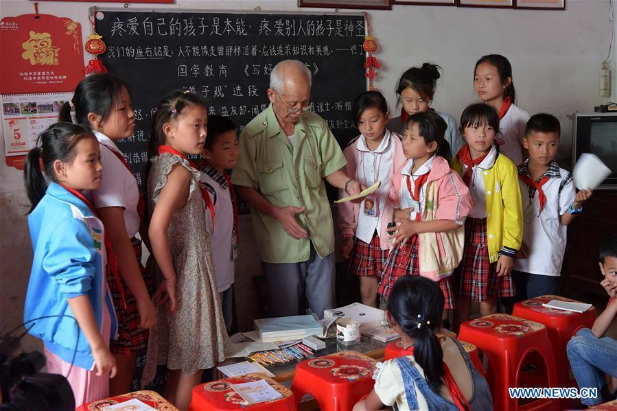 Miao Yanxiang awards children doing well on homework with prizes he bought at the caring station for left-behind children at his home in Shibu Town, Nanchang City of east China\'s Jiangxi Province, May 23, 2018. Miao, over 70, established a caring station for left-behind children at his own house in 2009, where he provided free place for children to do homework and study after school. Having received more than 3,000 children over the past nine years, Miao is satisfied with his voluntary work as he see the progress of the children. (Xinhua/Peng Zhaozhi)