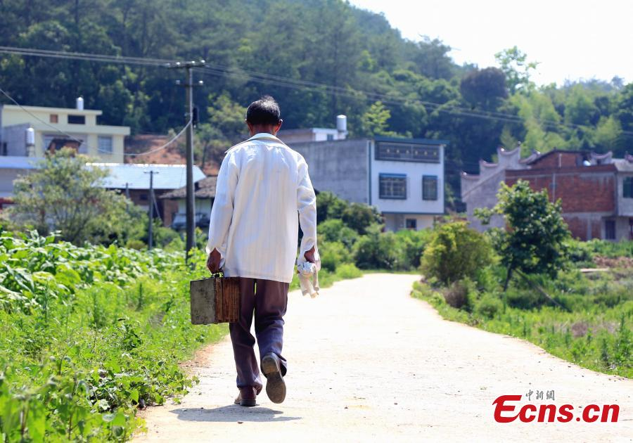 Barber Hu Daofa walks in a village in Zhuangbu Countryside, Huichang County, East China's Jiangxi Province. Hu, 73, started travelling around nearby villages offering door-to-door haircutting, shaving, and ear-cleaning in 1966, charging an annual fee of 130 yuan for three visits a month. Hu can't ride a bicycle, so he walks. Most of his customers are children and elderly people. (Photo: China News Service/Jiang Tao)