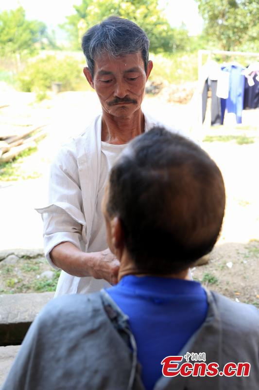 Barber Hu Daofa cuts a man's hair at a village in Zhuangbu Countryside, Huichang County, East China's Jiangxi Province. Hu, 73, started travelling around nearby villages offering door-to-door haircutting, shaving, and ear-cleaning in 1966, charging an annual fee of 130 yuan for three visits a month. Hu can't ride a bicycle, so he walks. Most of his customers are children and elderly people. (Photo: China News Service/Jiang Tao)
