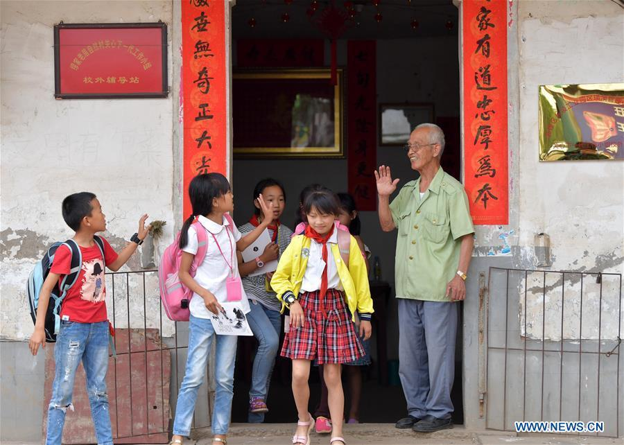 Miao Yanxiang farewells children at the caring station for left-behind children at his home in Shibu Town, Nanchang City of east China\'s Jiangxi Province, May 23, 2018. Miao, over 70, established a caring station for left-behind children at his own house in 2009, where he provided free place for children to do homework and study after school. Having received more than 3,000 children over the past nine years, Miao is satisfied with his voluntary work as he see the progress of the children. (Xinhua/Peng Zhaozhi)