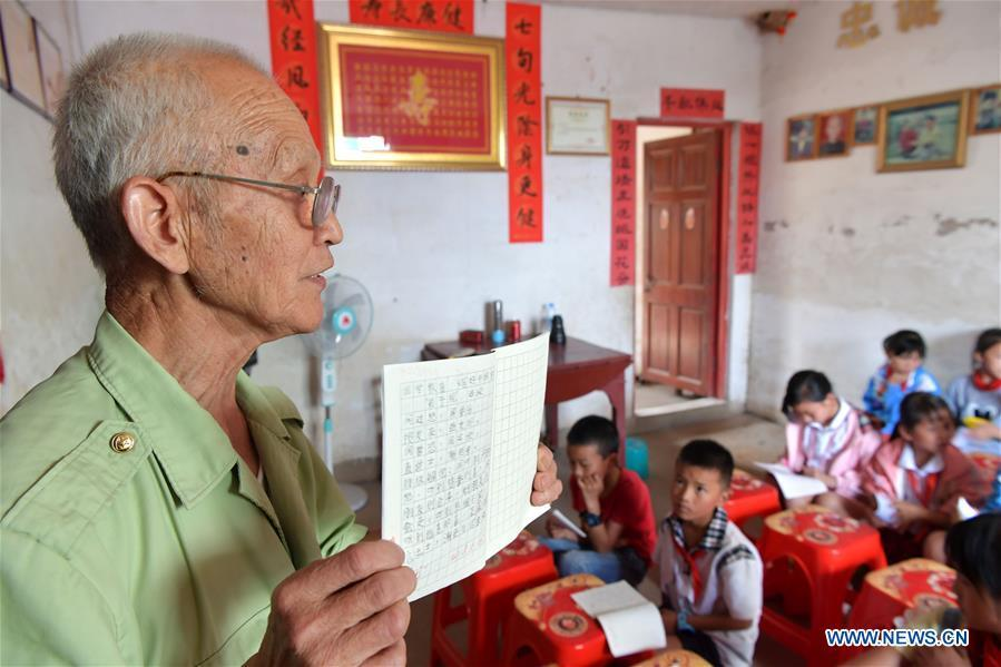 Miao Yanxiang displays well-done homework at the caring station for left-behind children at his home in Shibu Town, Nanchang City of east China\'s Jiangxi Province, May 23, 2018. Miao, over 70, established a caring station for left-behind children at his own house in 2009, where he provided free place for children to do homework and study after school. Having received more than 3,000 children over the past nine years, Miao is satisfied with his voluntary work as he see the progress of the children. (Xinhua/Peng Zhaozhi)