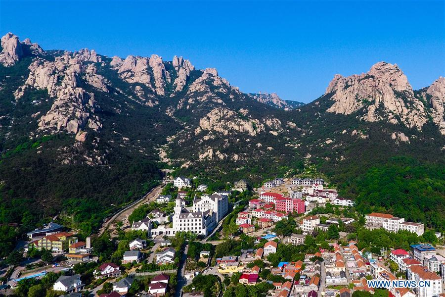 Aerial photo taken on May 19, 2018 shows a scene of a village at the foot of the Laoshan Mountain in Qingdao, east China\'s Shandong Province. (Xinhua/Guo Xulei)