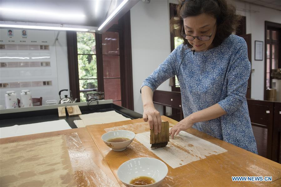 Yan Jingshu dyes restoration paper at Zhejiang Library in Hangzhou, east China\'s Zhejiang Province, May 23, 2018. Yan, 55, has worked in the national level ancient book restoration center of the library for 38 years. She and her colleagues collected more than 200 types of paper to restore ancient books. (Xinhua/Weng Xinyang)