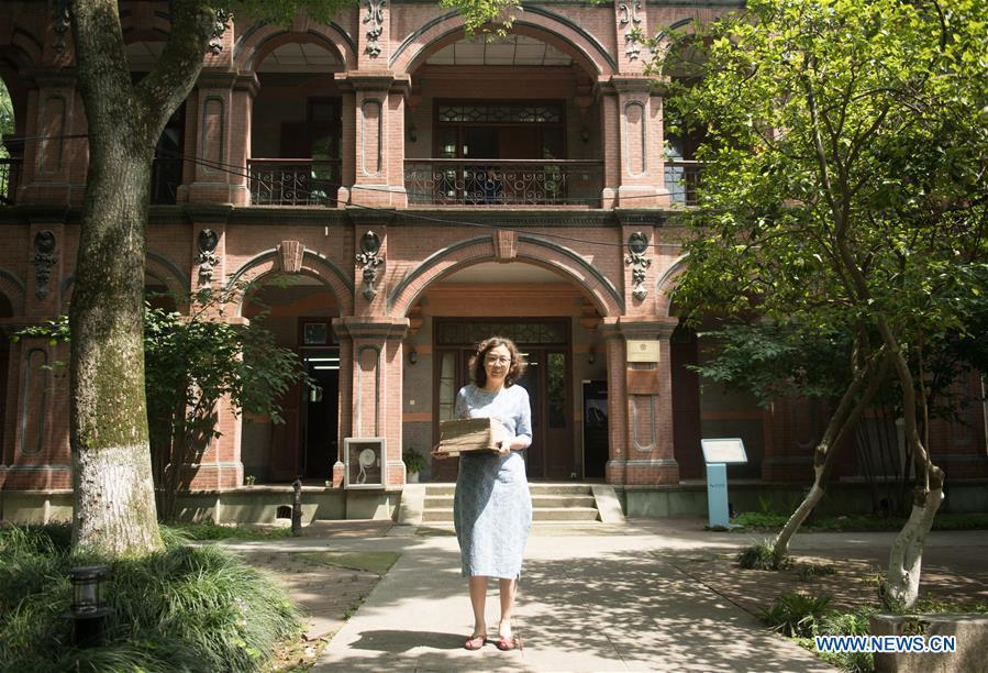 Yan Jingshu poses for photo in front of the ancient book restoration center of Zhejiang Library in Hangzhou, east China\'s Zhejiang Province, May 23, 2018. Yan, 55, has worked in the national level ancient book restoration center of the library for 38 years. She and her colleagues collected more than 200 types of paper to restore ancient books. (Xinhua/Weng Xinyang)