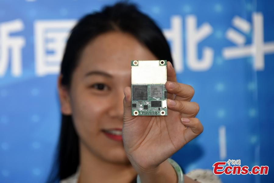 A worker shows radio frequency chip Hengxing-1 at the ninth China Satellite Navigation Conference in Harbin, capital of Heilongjiang province, May 24, 2018. The chip, which could be used for receiving and sending signals from Beidou-3 satellites, is developed by Guangzhou-based company Hi-Target Surveying Instrument. This chip, of which the Hi-Target company has independent intellectual property rights, adopts a highly integrated design and is available for use in the current four navigation systems from the US, Russia, Europe and China. It\'s estimated that Hengxing-1 will be put into production in the second half of 2018 and largely replace imported chips by the end of this year, according to the company. (Photo: China News Service/ Sunnn Zifa)