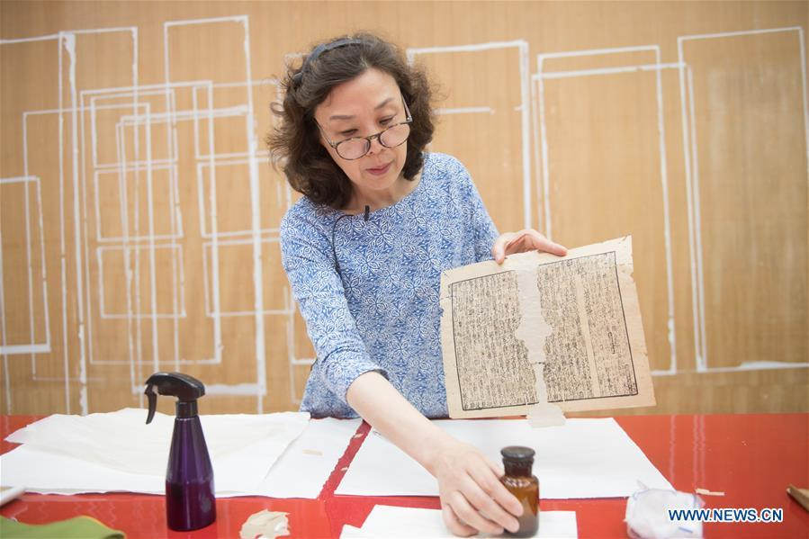 Yan Jingshu shows an ancient book under restoration at Zhejiang Library in Hangzhou, east China\'s Zhejiang Province, May 23, 2018. Yan, 55, has worked in the national level ancient book restoration center of the library for 38 years. She and her colleagues collected more than 200 types of paper to restore ancient books. (Xinhua/Weng Xinyang)