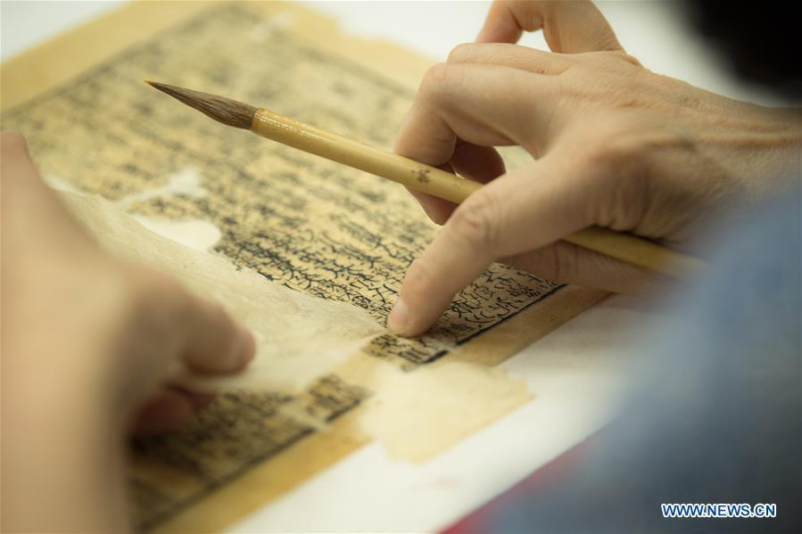 Yan Jingshu restores an ancient book at Zhejiang Library in Hangzhou, east China\'s Zhejiang Province, May 23, 2018. Yan, 55, has worked in the national level ancient book restoration center of the library for 38 years. She and her colleagues collected more than 200 types of paper to restore ancient books. (Xinhua/Weng Xinyang)