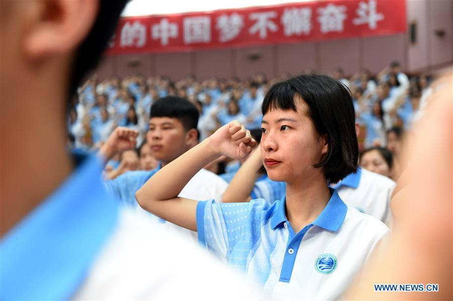 Volunteers take an oath during a launch ceremony for the volunteer program for the upcoming Shanghai Cooperation Organization (SCO) summit in Qingdao, east China\'s Shandong Province, May 24, 2018. About 2,000 volunteers will offer services such as assisting with guests\' arrival and departure, translation, and media requests during the 18th summit of the SCO. (Xinhua/Li Ziheng)