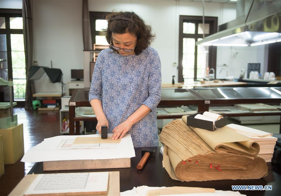 Yan Jingshu planishes an ancient book after restoration at Zhejiang Library in Hangzhou, east China\'s Zhejiang Province, May 23, 2018. Yan, 55, has worked in the national level ancient book restoration center of the library for 38 years. She and her colleagues collected more than 200 types of paper to restore ancient books. (Xinhua/Weng Xinyang)