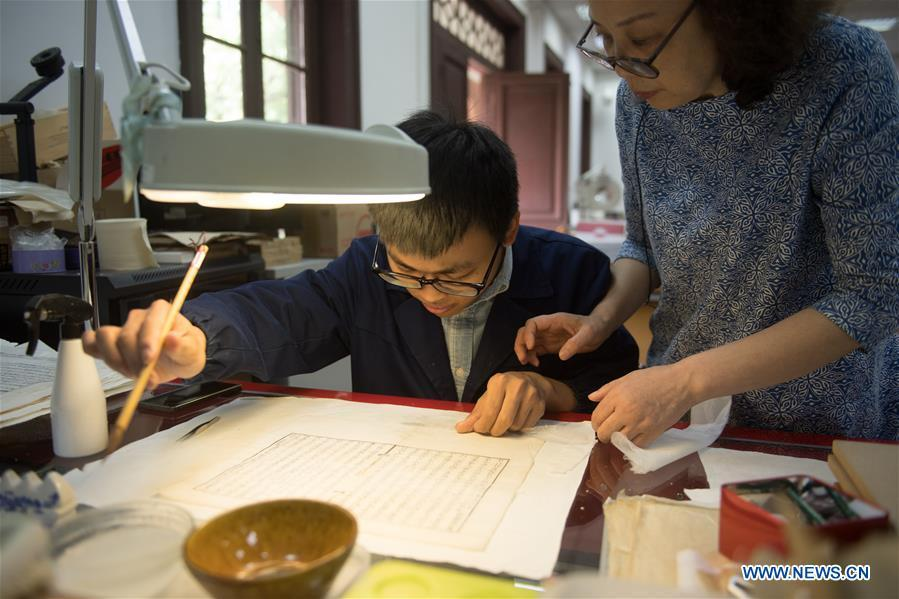 Yan Jingshu (R) instructs an apprentice in ancient book restoration at Zhejiang Library in Hangzhou, east China\'s Zhejiang Province, May 23, 2018. Yan, 55, has worked in the national level ancient book restoration center of the library for 38 years. She and her colleagues collected more than 200 types of paper to restore ancient books. (Xinhua/Weng Xinyang)