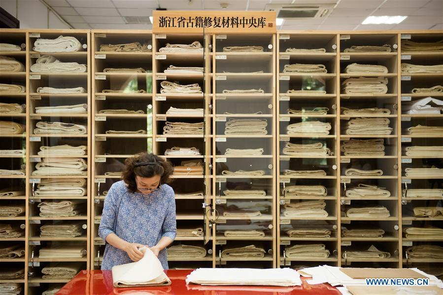 Yan Jingshu selects restoration paper at Zhejiang Library in Hangzhou, east China\'s Zhejiang Province, May 23, 2018. Yan, 55, has worked in the national level ancient book restoration center of the library for 38 years. She and her colleagues collected more than 200 types of paper to restore ancient books. (Xinhua/Weng Xinyang)