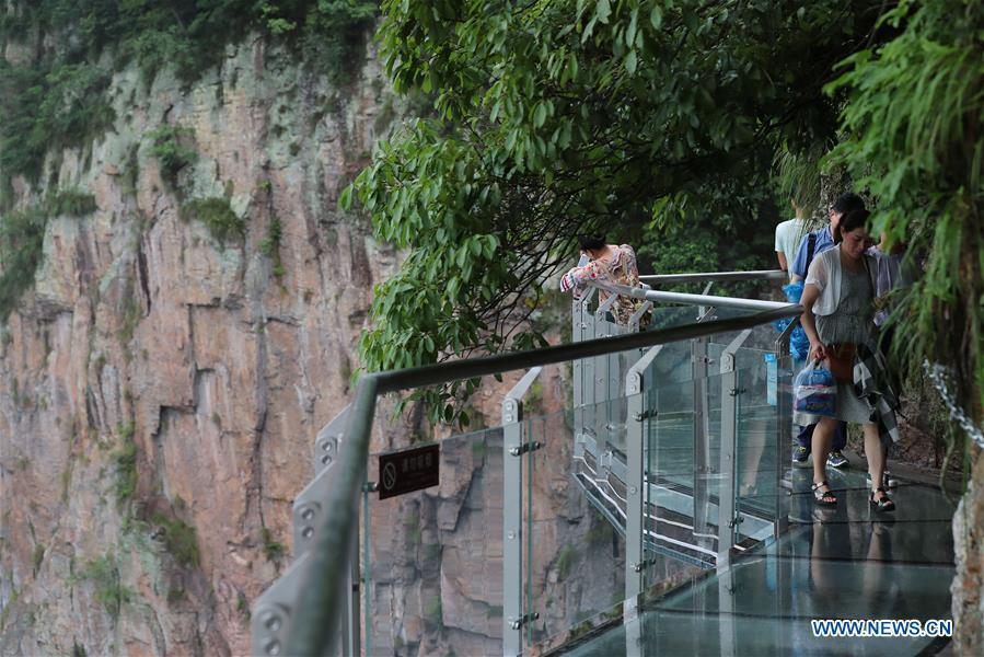 People walk on the Lingyundu glass trestle in the Xuedou Mountain in Ningbo City, east China\'s Zhejiang Province, May 26, 2018. The glass trestle was opened to tourists on Saturday. (Xinhua/Zhang Peijian)