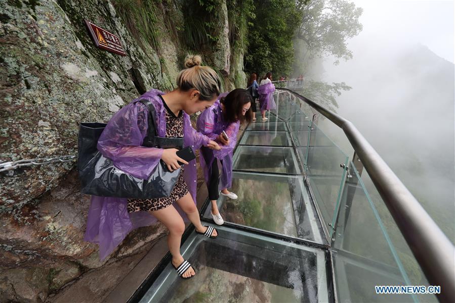 People look down the cliff through the Lingyundu glass trestle in the Xuedou Mountain in Ningbo City, east China\'s Zhejiang Province, May 26, 2018. The glass trestle was opened to tourists on Saturday. (Xinhua/Zhang Peijian)