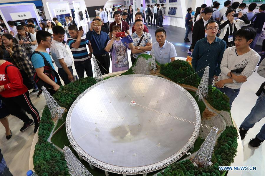People look at a model of China\'s Five-hundred-meter Aperture Spherical Radio Telescope (FAST), the world\'s largest single-dish radio telescope, during the International Big Data Industry Expo in Guiyang, capital of southwest China\'s Guizhou Province, May 26, 2018. The four-day expo opened here on Saturday, attracting over 40,000 participants from nearly 30 countries. (Xinhua/Liu Xu)