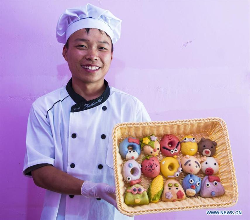 A villager shows buns made from vegetable and fruit in Zhaozijian Village, Zaoqiang County of north China\'s Hebei Province, May 26, 2018. Buns made from pumpkin, spinach, cabbage and other vegetable and fruit in Zaoqiang County are popular in supermarkets and online shops. (Xinhua/Li Xiaoguo)