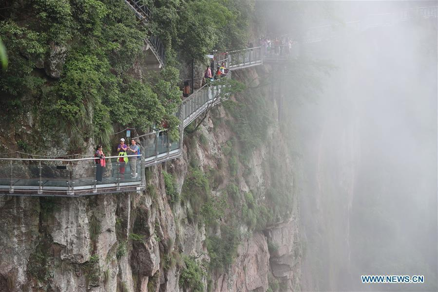 People are seen on the Lingyundu glass trestle in the Xuedou Mountain in Ningbo City, east China\'s Zhejiang Province, May 26, 2018. The glass trestle was opened to tourists on Saturday. (Xinhua/Zhang Peijian)