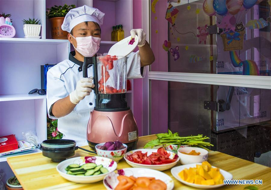 A villager makes vegetable and fruit juice in Zhaozijian Village, Zaoqiang County of north China\'s Hebei Province, May 26, 2018. Buns made from pumpkin, spinach, cabbage and other vegetable and fruit in Zaoqiang County are popular in supermarkets and online shops. (Xinhua/Li Xiaoguo)