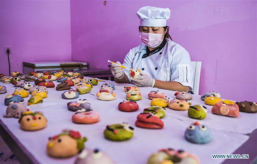 A villager makes vegetable and fruit buns in Zhaozijian Village, Zaoqiang County of north China\'s Hebei Province, May 26, 2018. Buns made from pumpkin, spinach, cabbage and other vegetable and fruit in Zaoqiang County are popular in supermarkets and online shops. (Xinhua/Li Xiaoguo)