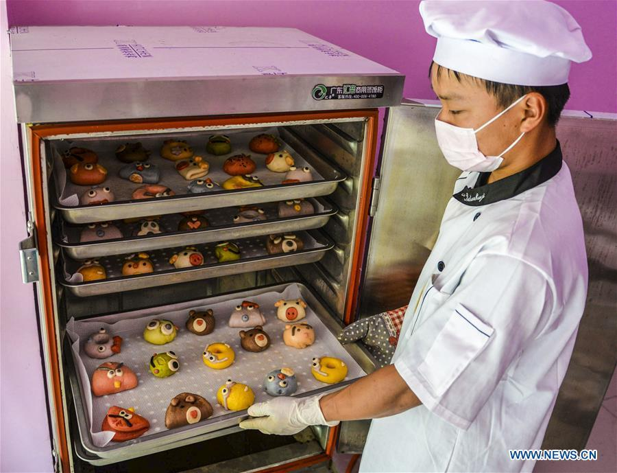 A villager takes out steamed buns made from vegetable and fruit in Zhaozijian Village, Zaoqiang County of north China\'s Hebei Province, May 26, 2018. Buns made from pumpkin, spinach, cabbage and other vegetable and fruit in Zaoqiang County are popular in supermarkets and online shops. (Xinhua/Li Xiaoguo)