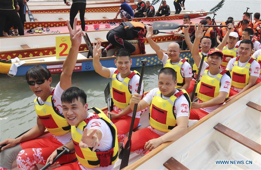 Contestants wave hands before a dragon boat match at a water park of Huichang lake in Wenzhou, east China\'s Zhejiang Province, May 26, 2018. (Xinhua/Su Qiaojiang)