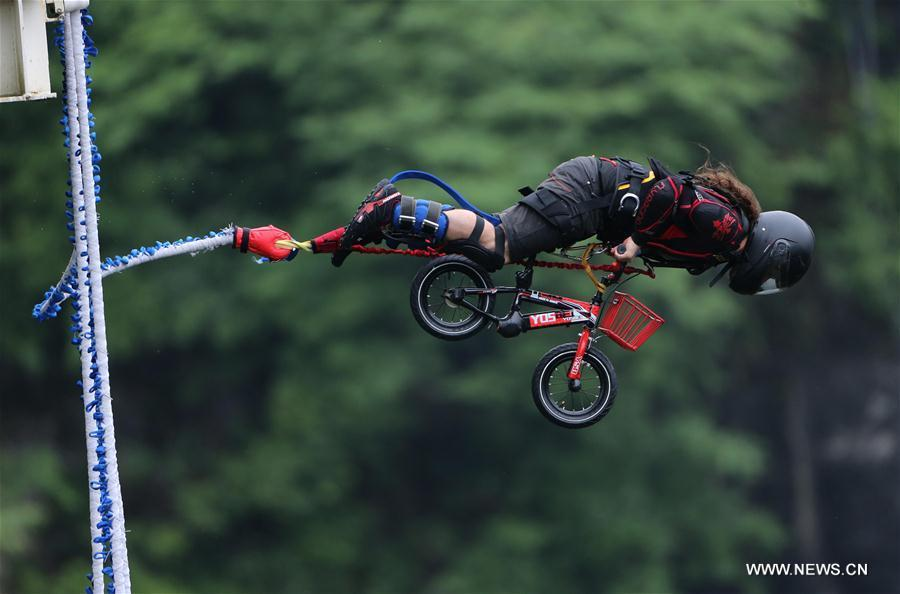 An enthusiast goes bungee jumping from Zhangjiajie Grand Canyon\'s glass-bottom bridge, during a challenge in Zhangjiajie scenic spot, central China\'s Hunan Province, May 26, 2018. Enthusiasts from Russia, Australia, Britain and other countries and regions participated in the challenge on Saturday. (Xinhua/Zhou Guoqiang)