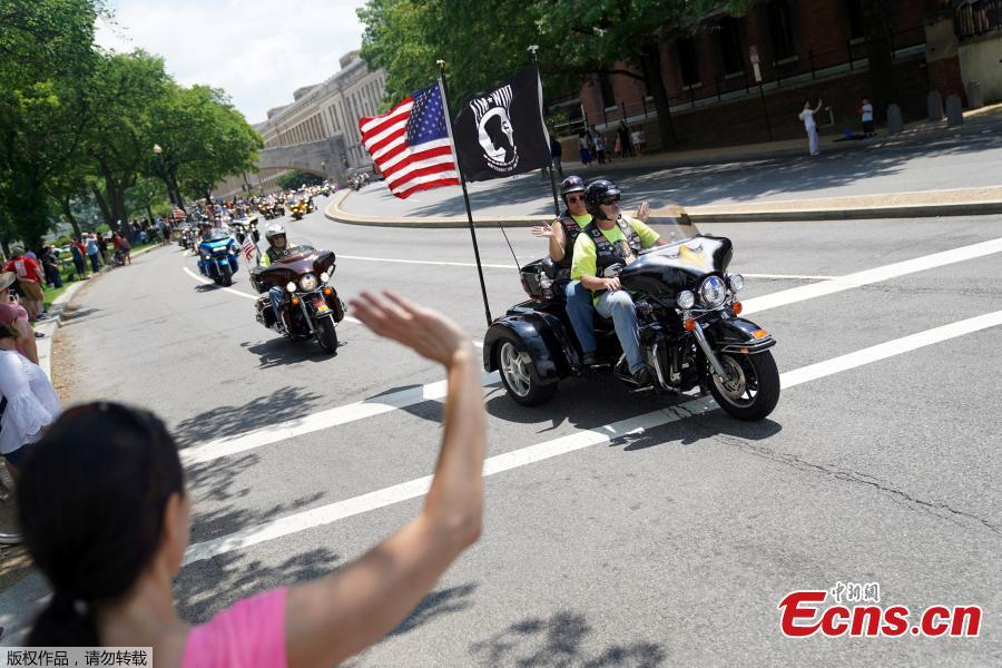 A woman waves at riders as thousands of military veterans and their supporters participate in the 31st annual Rolling Thunder motorcycle rally and Memorial Day weekend \